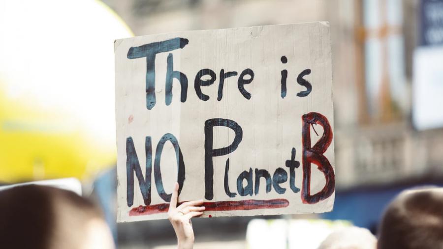 """På skiltet står der på engelsk """"There is NO Planet B"""", hvilket kan oversættes til """"Der er INGEN Planet B""""."""